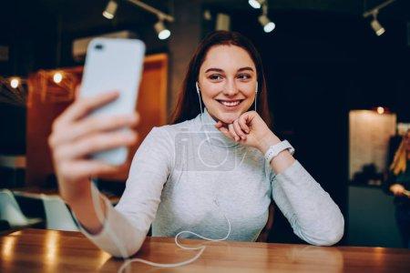 Photo pour Jolie fille gaie posant pour selfie sur smartphone caméra écoute playlist préférée dans les écouteurs, souriant hipster femme prenant des photos en appréciant la musique via lecteur cellulaire pendant les loisirs dans caf - image libre de droit