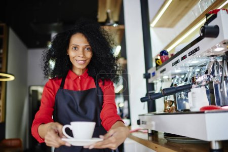 Photo for Half length portrait of african american positive barista giving tasty coffee and smiling at camera.Cheerful waitress in apron holding cup of aroma beverage standing at bar near machine in oen cafe - Royalty Free Image