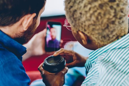 Photo for Selective focus on multicultural friends holding modern smartphone and watching videos in social networks using 4G internet.Back view of hipster guys updating application on digital cellular - Royalty Free Image