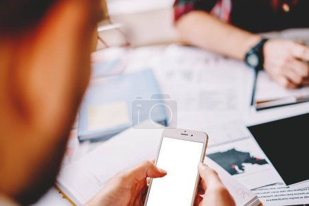 Selective focus on modern smartphone device with blank screen for your advertising content.Cropped view of young man updating profile on mobile phone with mock up area for internet text message