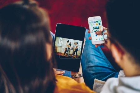 Photo pour Recadrée vue arrière de la jeune femme faisant des achats en ligne sur touchpad moderne tandis que guy de hipster vérifie les mails sur smartphone. Couple amoureux la visualisation de photos sur la tablette et le partage de médias sur le téléphone - image libre de droit