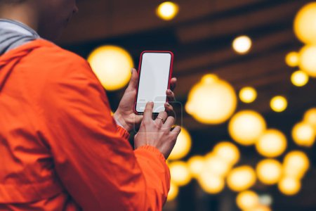 Photo for Women's hands hold mobile phone with   big copy space touch screen outdoors with evening bokeh light of city on background. Close up view of female person using smartphone with blank advertise display - Royalty Free Image