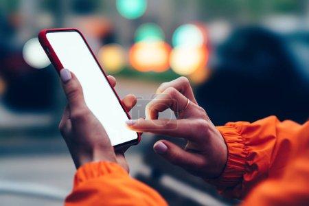 Photo pour Bouchent la vue des mains féminines tenant téléphone portable retouche simulé un écran blanc avec le doigt. Personnes qui utilisent des app sur smartphone sur rue avec bokeh floue lumières de la ville. Message de SMS dans les réseaux sociaux - image libre de droit