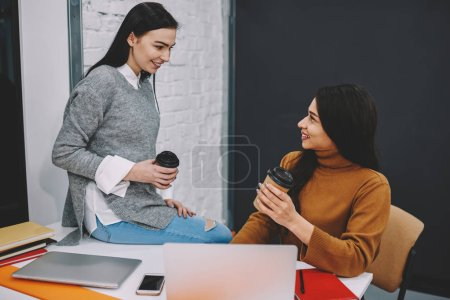 Positive women having friendly talk on coffee break enjoying communication about work in office, smiling girls having conversation about education in college on leisure time share information