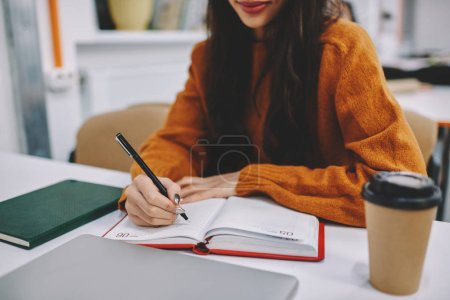 Cropped image of talented woman student making notations to notepad while preparing for coursework project sitting in campus, talented creative hipster girl recording information using black pen