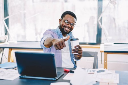 Prosperous african american hipster guy showing ok sign satisfied with aroma coffee on work break in office, portrait of smiling dark skinned freelancer with thumb up gesture sitting happy at deskto