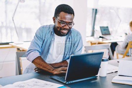 Photo pour Élève de sexe masculin afro-américain gai rire tout en regardant film drôle en ligne via netbook sur le campus, prospère pigiste mâle satisfait avec succès dans les affaires en ligne lecture nouvelles sur lapto - image libre de droit