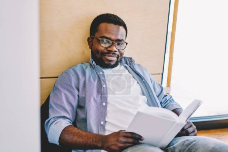 Portrait of thoughtful african american man in eyewear for vision correction spending free time on interesting book, dark skinned hipster guy holding bestseller looking at camera on leisur