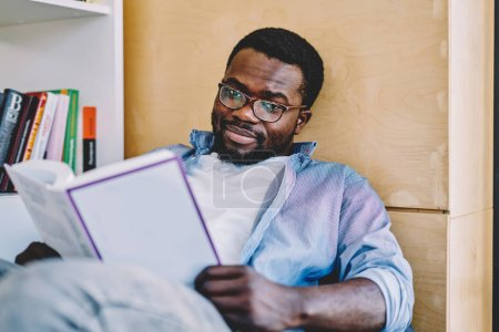 Portrait of serious african american hipster guy in eyewear for vision protection disappointed with book plot, unhappy pensive dark skinned male looking at camera holding bestseller on leisur