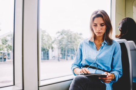 Pensive young woman listening audio player online on website in earphones connected to touch pad device sitting in tram.Hipster blogger watching videos on tablet via free transport wireless internet