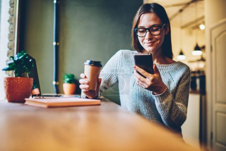 Cheerful hipster blogger with coffee to go in hands reading incoming sms message on smartphone connected to free wifi.Positive young student watching broadcasting online on modern mobile phone