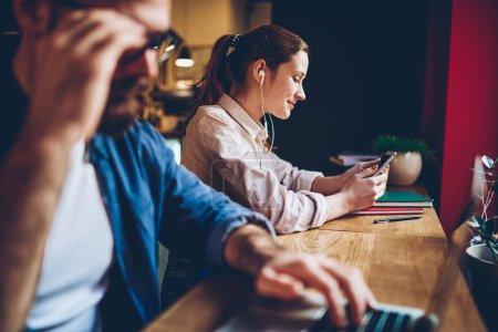 Photo pour Jeune gai écoute audiobook téléchargé sur smartphone moderne écouteurs assis dans coworking. Souriant hipster blogger femelle choisissant musique application à installer sur téléphone mobile - image libre de droit