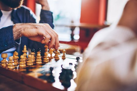 Photo for Cropped image of male hands making move of white pawn on wooden chessboard during strategic game in chess sitting in coworking.Selective focus on sport battle in tactic play with chess - Royalty Free Image