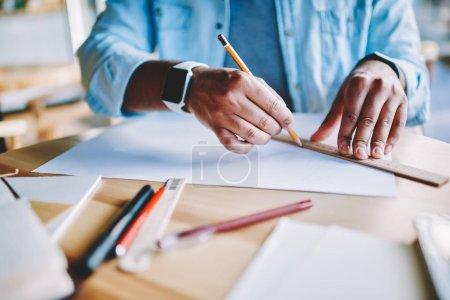 Photo pour Image recadrée des mains de l'architecte avec un crayon de maintien smartwatch et dessin croquis du plan de construction sur papier blanc. Planification de traçage concepteur sur bureau en bois avec équipement - image libre de droit