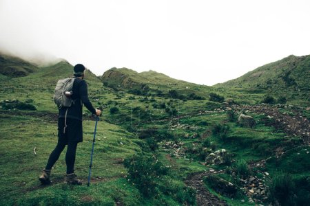 Back view of tourist dressed in active wear climbing up on green hight hill exploring wilderness nature.Traveller with backpack using trekking sticks during wanderlust on mountains