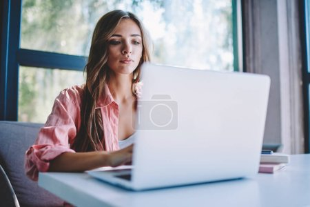 Concentrated young woman searching information on internet websites for course work using modern laptop with wireless connection in cafe.Pensive female freelancer working at netbook in coworking