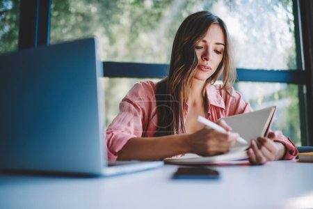 Photo for Pensive young businesswoman making notes of working plan in notepad sitting at laptop computer in coworking space.Hipster student writing homework and preparing for studying seminar at netbook - Royalty Free Image