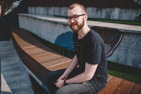 Portrait of caucasian bearded young man in eyeglasses for vision correction smiling at camera while sitting in urban setting in city.Positive hipster guy in eyewear spending free time on street