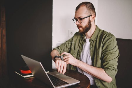 Pensive bearded young man checking time on smartwatch during working at laptop computer in coffee shop.Concentrated hipster student managing clock on wristwatch while preparing for exam at netbook