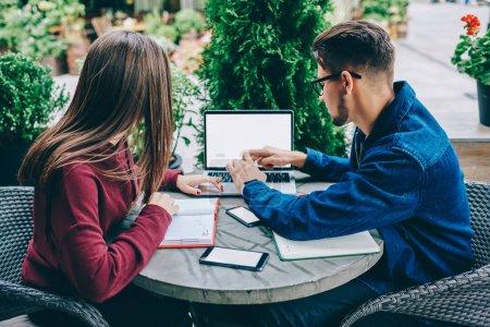 Photo pour Vue arrière de collègues masculins et féminins, regarder webinaire sur ordinateur portable avec écran, assis sur la terrasse du café, jeunes étudiants à l'aide de connexion wifi pour navigation vidéo sur netbook sur loisirs maquettes - image libre de droit