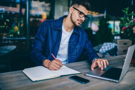Photo pour Jeune étudiant caucasien masculin dans les lunettes d'apprentissage cours en ligne via ordinateur portable et de prendre des notes, gars hipster coûteux notant des informations provenant de réseaux en utilisant netbook pour regarder tutoriel - image libre de droit