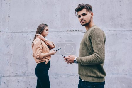 Male and female hipsters walking outdoors using mobile phones addicted to modern device and online chatting, guy looking at camera holding cellphone while woman on background strolling with cellular