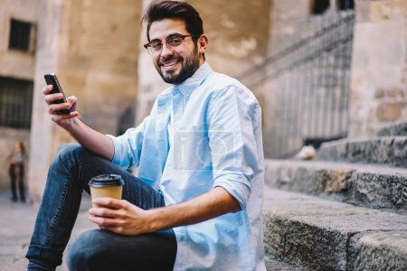 Portrait of cheerful hipster guy holding smartphone for chatting in social networks sitting at street with coffee to go, happy male in trendy spectacles spending free time in town using cellular