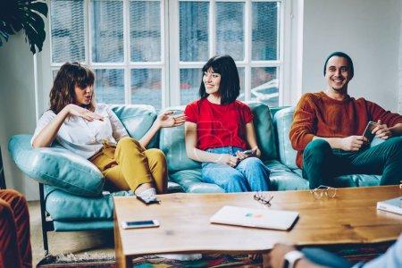 Hipster dziewczyna skrzyżowane ręce wyjaśniające informacje podczas gry z przyjaciółmi w nowoczesne apartment.positive młodych ludzi ubranych w odzież codzienna, komunikują się ze sobą cieszyć czas rekreacji