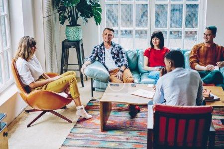 Photo pour Jeunes gens multiculturels positifs habillés en vêtements décontractés passer du temps libre ensemble jouer au jeu dans un appartement moderne avec intérieur élégant. hipsters joyeux communiquant entre eux - image libre de droit