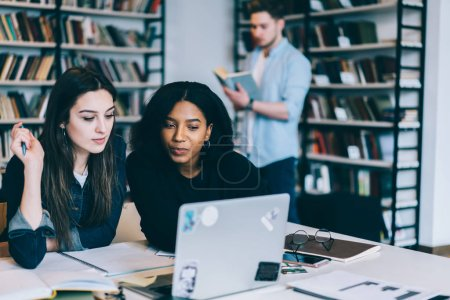 Photo for Young multiracial female students sitting together in library watching tutorial online via wireless internet  learning, clever young women concentrated on reading information from web making research - Royalty Free Image
