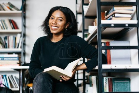 Portrait of cheerful african american girl smiling satisfied with interesting book find in college library, young dark skinned woman enjoying free time in bookstore reading literature look at camera