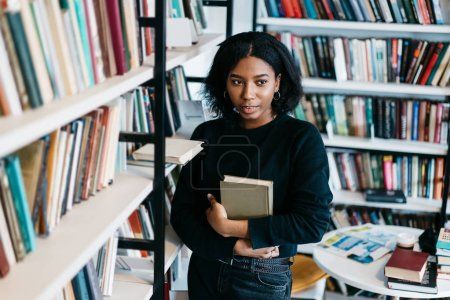 Portrait of pensive african american young woman holding book for reading spending time in library fond of literature, serious dark skinned female with textbook standing near shelves in bookstore