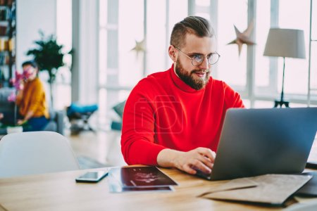 Skilled male freelancer working at home interior using laptop computer and wireless internet sitting at desktop, hipster guy watching online video on netbook, man checking mail and blogging
