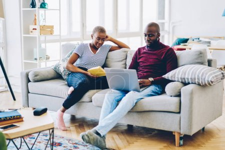 Photo for Young african american family spending time at home interior resting with reading book and using laptop computer,hipster guy watching video on netbook sitting next to his girlfriend enjoy novel - Royalty Free Image