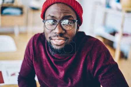 Close up image of dark skinned hipster guy in trendy hat and eyewear for vision protection looking at camera, portrait of smiling bearded male satisfied with stylish spectacles sitting indoors