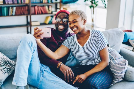 Cheerful dark skinned couple in love resting at home interior posing for selfie on smartphone camera,happy young hipsters making image on modern mobile phone laughing at living room togethe