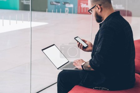 Photo for Pensive bearded hipster IT developer holding smartphone with blank screen area and reading notification on device during working remotely at netbook with copy space.Young man sharing media on gadgets - Royalty Free Image
