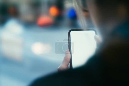 Cropped back view of young woman holding modern smartphone with blank screen area for your internet content or website.Selective focus on digital cellular with copy space area for web page