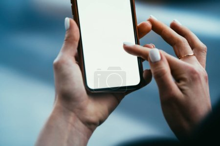 Photo for Cropped view of young woman's hands holding digital smartphone and typing with finger text message on blank display of device using high speed 4G internet connection for online chat - Royalty Free Image