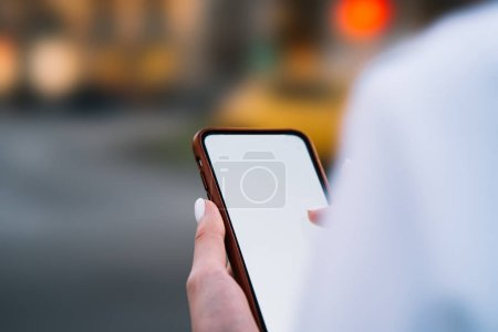 Photo for Cropped view of modern smartphone device with blank screen area for your internet advertising and website on blurred background.Digital mobile phone with mock up area in woman's hands - Royalty Free Image