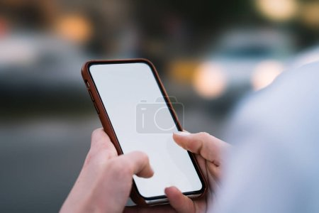 Photo for Cropped view of woman's hands holding smartphone with blank screen area for your internet content on website.Selective focus on female fingers typing text message on telephone with mock up area - Royalty Free Image