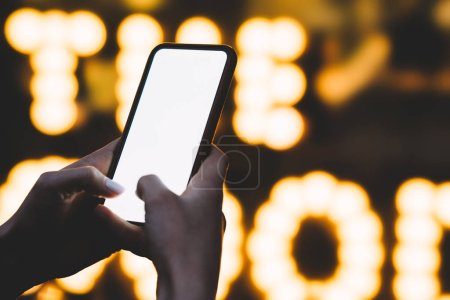Photo for Cropped view of woman's hands holding smartphone in hands and typing text with fingers on blank display of modern device using internet connection on background with night lights and illumination - Royalty Free Image