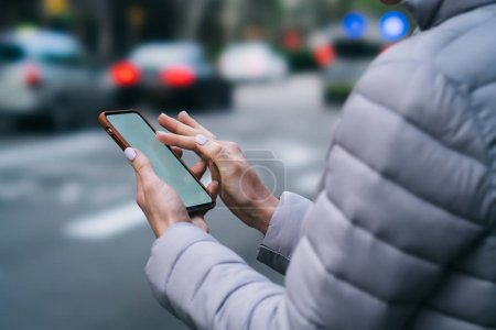 Photo for Cropped view of female fingers touching on display of modern smartphone device using 4G internet connection on blurred background of urban setting.Woman's hands holding cellular and making payment - Royalty Free Image