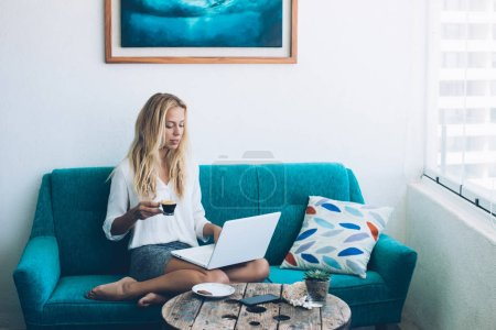 Photo for Caucasian young woman on cozy couch making online booking on website via laptop computer, attractive hipster girl planning vacations via application on modern netbook while connected to home wifi - Royalty Free Image