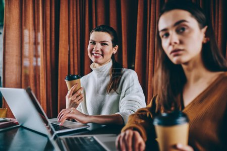 Portrait of positive smiling female teenager holding cup of takeaway coffee spending time with friend on leisure, two successful it professional enjoying distance job with netbooks at cafeteria