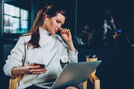 Mujer encantadora caucásica ver webinar en ordenador portátil mientras navega por internet inalámbrico en smartphone, chicas hipster hermosa instalación aplicación bluetooth en netbook para compartir información