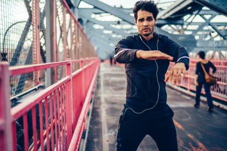 Young healthy man in sportswear doing cardio workout while listening audio book via headphones on city bridge, muscular hipster guy making effort during training outdoors and looking at camera