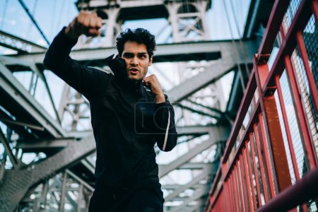 Serious man in tracksuit practicing and doing power punches on city bridge, concentrated sportsman training and boxing on workout process, concept of healthy lifestyle and motivation for goal