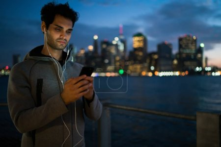 Healthy man searching exercises on sport website for evening training outdoors using 4g wireless connection on smartphone device, male runner in headphones choosing radio station on cellular
