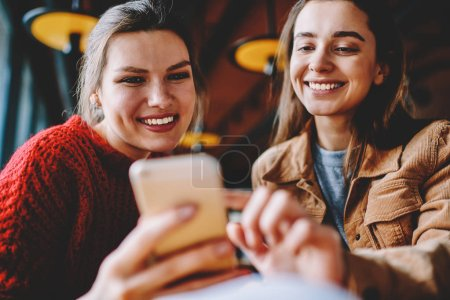 Two smiling female bloggers creating publication using photo application on mobile phone, happy millennial women chatting with friends via modern cellphone resting with technology on leisure